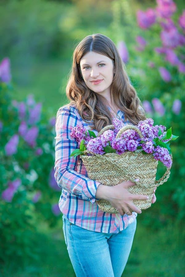 Den härliga kvinnan som tycker om lilaträdgården, den unga kvinnan med blommor i gräsplan, parkerar flicka som river lilan i träd royaltyfria foton