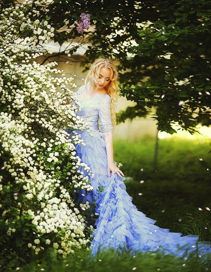 Den härliga kvinnan som tycker om lilaträdgården, den unga kvinnan med blommor i gräsplan, parkerar gladlynt gå för tonåring som  arkivbilder