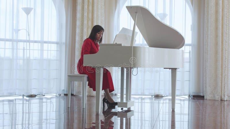 Den härliga kvinnan spelar ett vitt piano arkivbilder