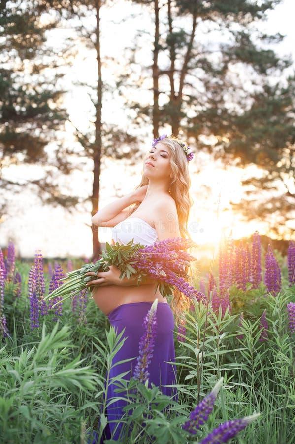 Den härliga kvinnan står omgav vid blommafältet royaltyfria foton