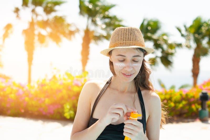 Den härliga kvinnan suddar framsidasunscreen på stranden för solskydd arkivfoton