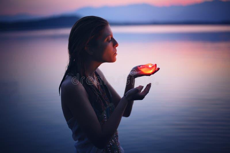 Den härliga kvinnan tände vid stearinljuset i purpurfärgat sjövatten royaltyfria foton