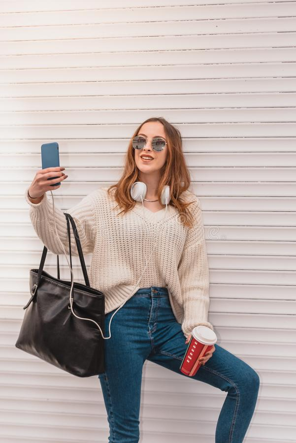 Den härliga kvinnan tar selfie, medan luta på en vägg arkivbilder
