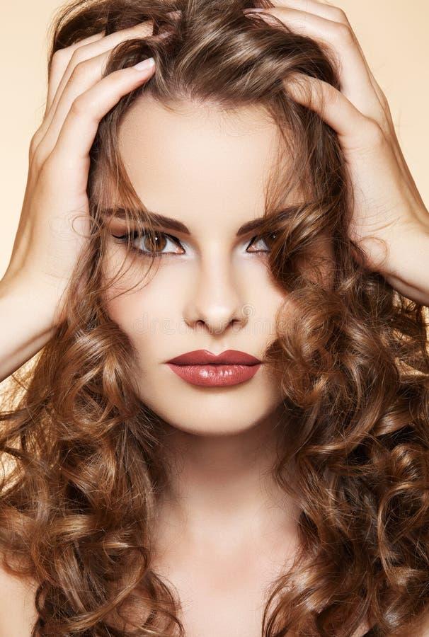 Den härliga kvinnan trycker på henne långt blankt lockigt hår arkivbilder