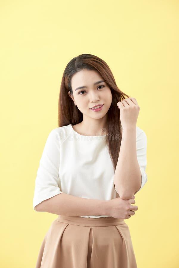 Den härliga kvinnan trycker på hennes vård- långa omsorg för rakt hår med leendeframsidan, asiatisk skönhetmodell royaltyfri fotografi