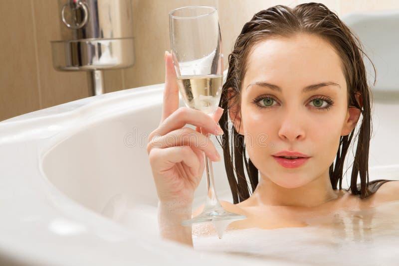 Den härliga kvinnan tycker om ett bad arkivfoto