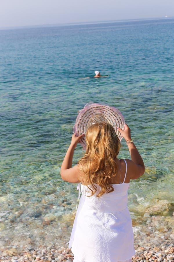 Den härliga kvinnan tycker om på stranden royaltyfri bild