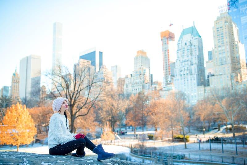 Den härliga kvinnan tycker om sikten av is-isbanan i Central Park och skyskrapor på Manhattan i New York City arkivbild