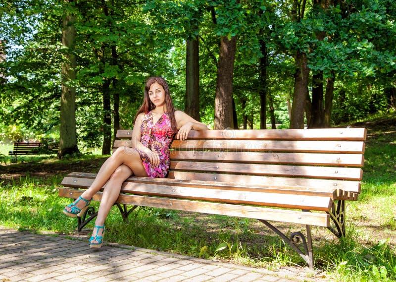 Den härliga kvinnan vilar sammanträde på en bänk parkerar in royaltyfria foton