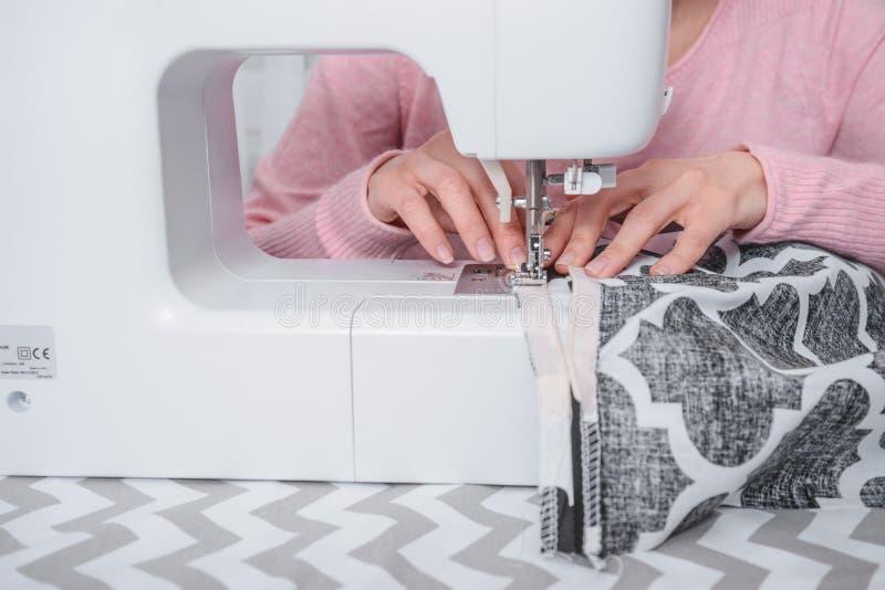 Den härliga kvinnasömmerskan syr på symaskinkläderna royaltyfria bilder