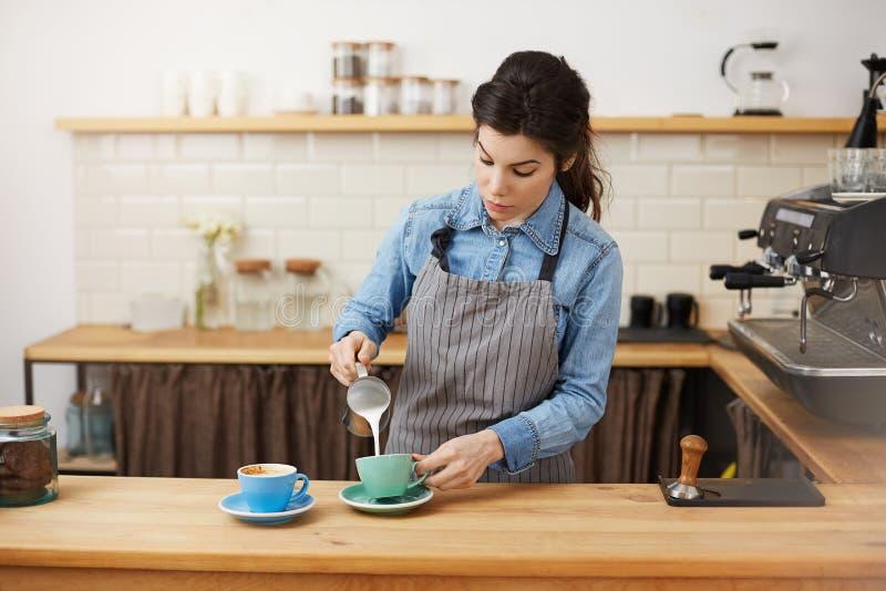 Den härliga kvinnliga baristaen häller mjölkar och att göra två cappuccino som ser koncentrerad royaltyfri fotografi