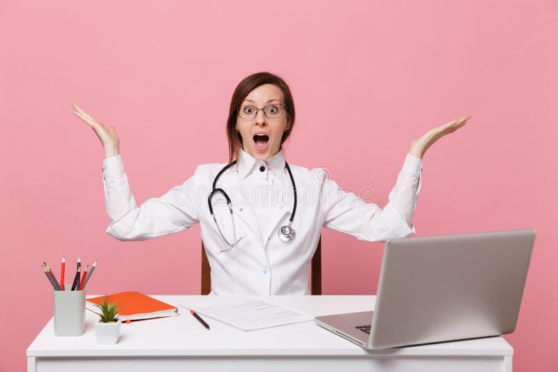 Den härliga kvinnliga doktorn sitter på skrivbordarbeten på datoren med det medicinska dokumentet i sjukhus på den pastellfärgade royaltyfria foton