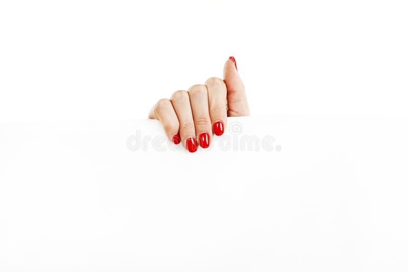 Den härliga kvinnliga handen med rött spikar att rymma ett tomt tecken arkivbilder