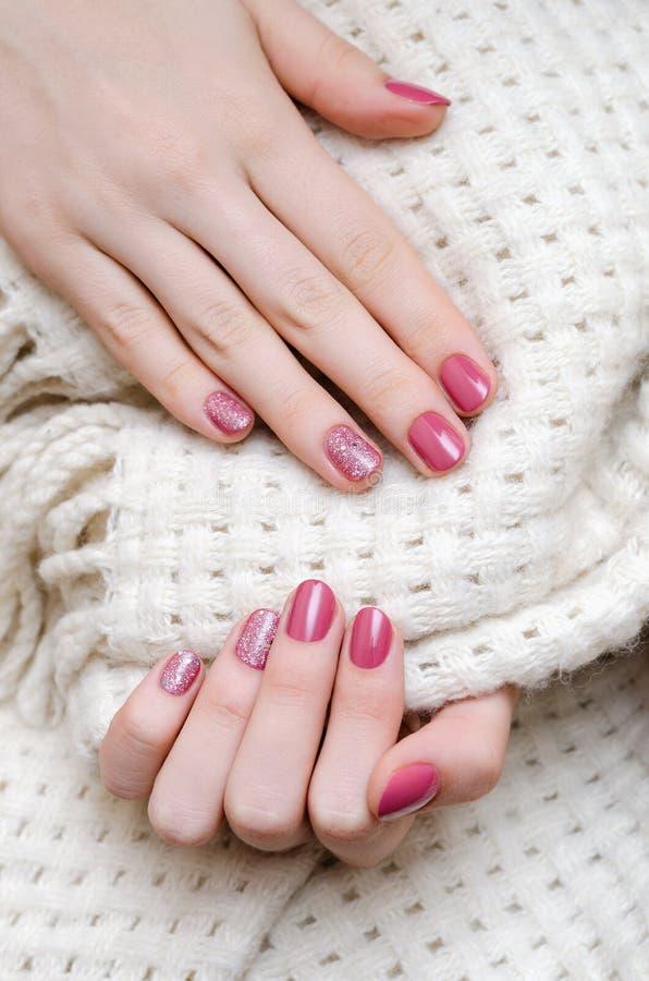 Den härliga kvinnliga handen med varma rosa färger spikar design arkivfoto