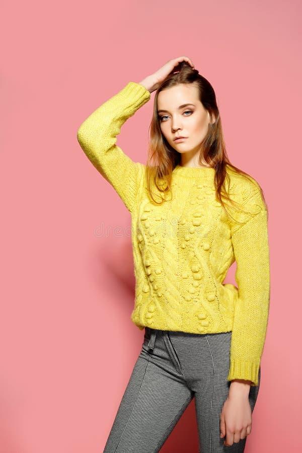 Den härliga kvinnliga modellen bär den tillfälliga comfrotable tröjan, poserar mot rosa bakgrund Copyspace arkivbilder
