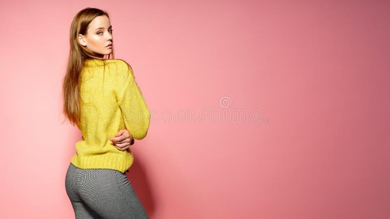 Den härliga kvinnliga modellen bär den tillfälliga comfrotable tröjan, poserar mot rosa bakgrund Copyspace royaltyfria bilder