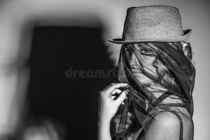 Den härliga kvinnliga modellen med hatten och skyler på framsidan med skugga arkivfoton