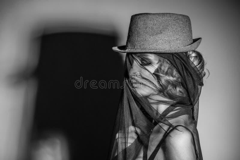 Den härliga kvinnliga modellen med hatten och skyler på framsidan med skugga arkivfoto