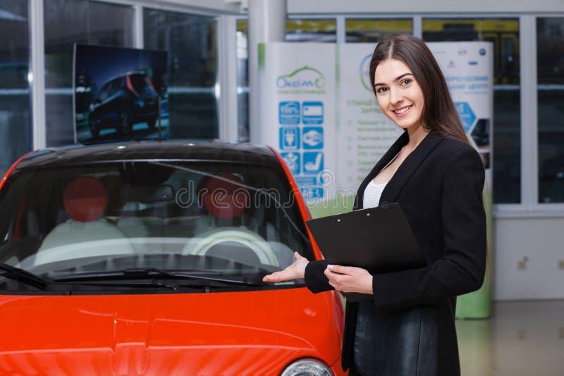 Den härliga kvinnliga säljaren visar bilen royaltyfria foton
