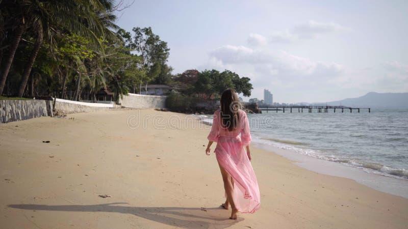 Den härliga kvinnlign i en lång framkallande rosa klänning går att gå runt om rotering på stranden på vaggar Närbild 4K arkivfoto