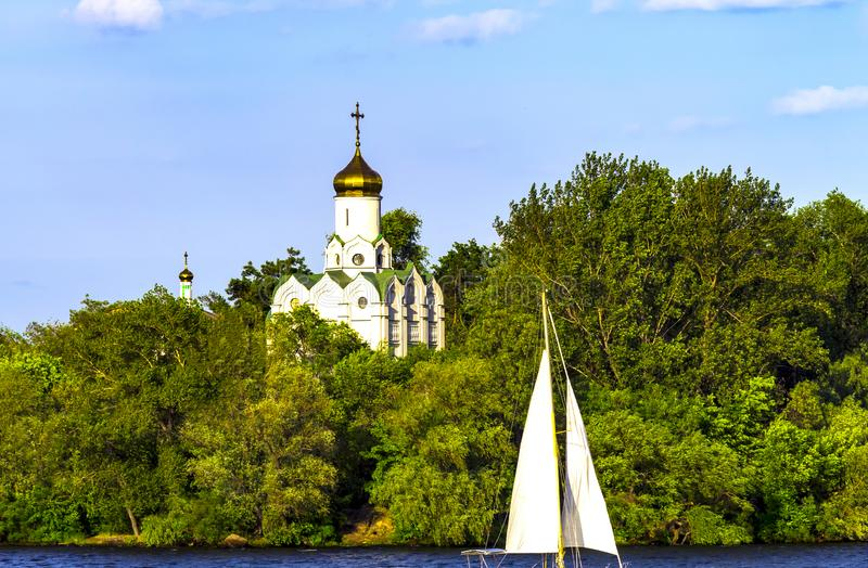 Den härliga kyrkan på ön, täckte med gröna träd och seglar fartyg på floden i vår och sommar Dnipro Dneprope royaltyfria foton