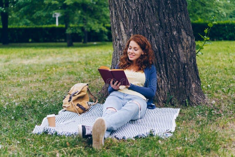 Den härliga läseboken för den unga kvinnan som sitter på filten under träd parkerar in, att le arkivfoto
