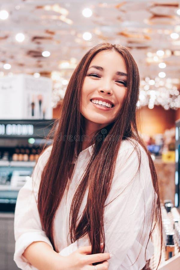 Den härliga långa hårasiatet som ler den unga kvinnan för flickan shoppar in, supermarket av skönhetsmedel, dofter, tullfri vara fotografering för bildbyråer