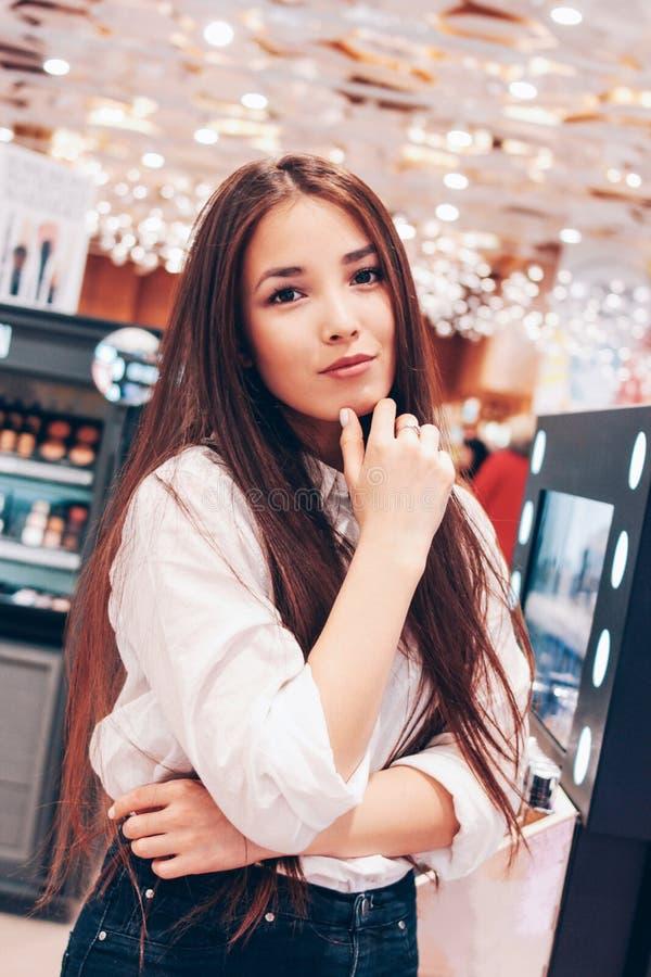 Den härliga långa hårasiatet som ler den unga kvinnan för flickan shoppar in, supermarket av skönhetsmedel, dofter, tullfri vara royaltyfria foton