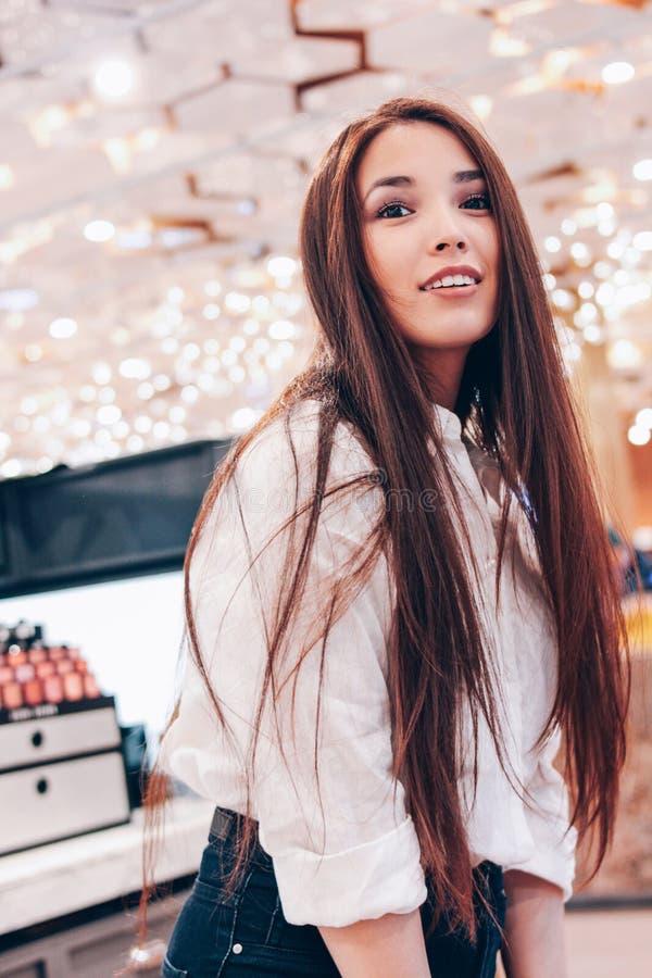 Den härliga långa hårasiatet som ler den unga kvinnan för flickan shoppar in, supermarket av skönhetsmedel, dofter, tullfri vara arkivbilder