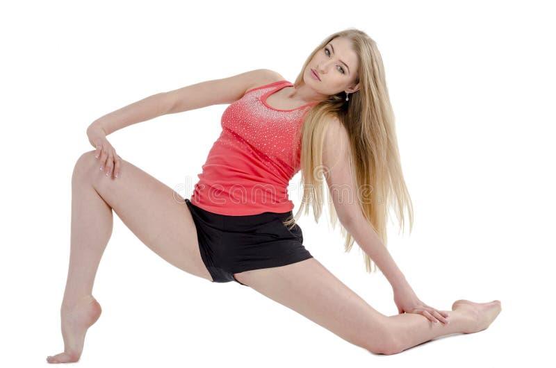Den härliga långhåriga gladlynta flickan är förlovad i gymnastiska övningar på golvet fotografering för bildbyråer