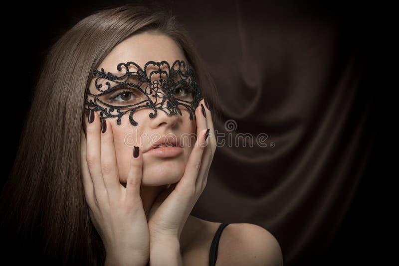 Den härliga ladyen i lacy svart maskerar fotografering för bildbyråer