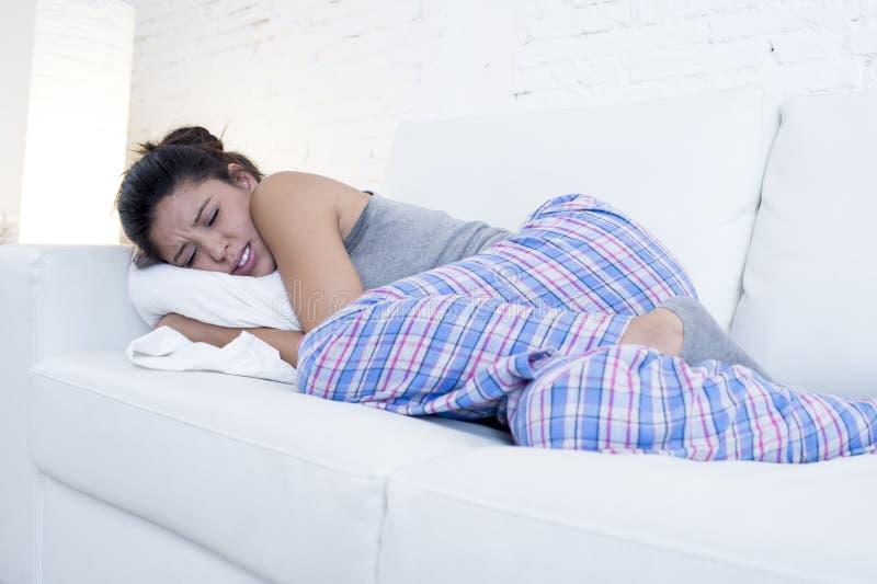 Den härliga latinamerikanska kvinnan i smärtsam uttrycksinnehavbuk som lider menstruations- period, smärtar arkivfoton