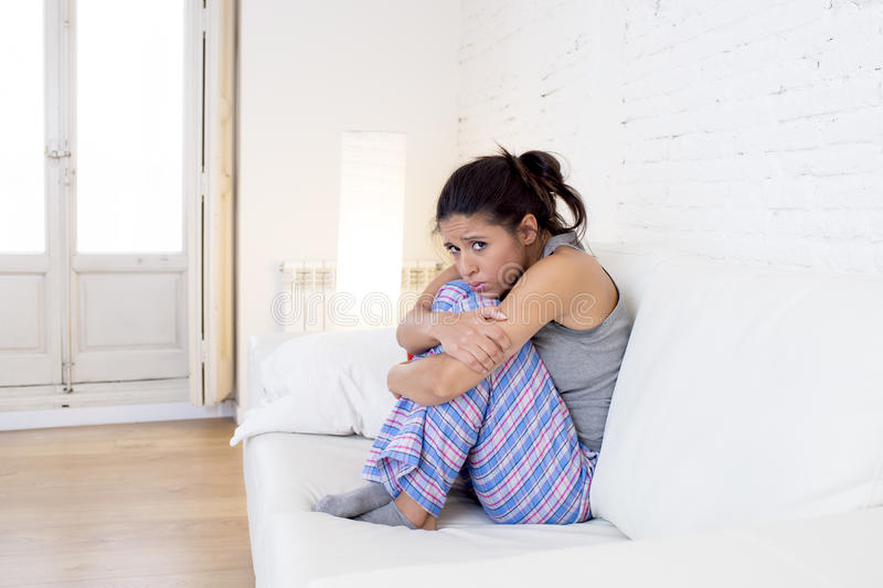 Den härliga latinamerikanska kvinnan i smärtsam uttrycksinnehavbuk som lider menstruations- period, smärtar royaltyfri foto