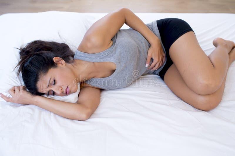 Den härliga latinamerikanska kvinnan i smärtsam uttrycksinnehavbuk som lider menstruations- period, smärtar royaltyfria bilder
