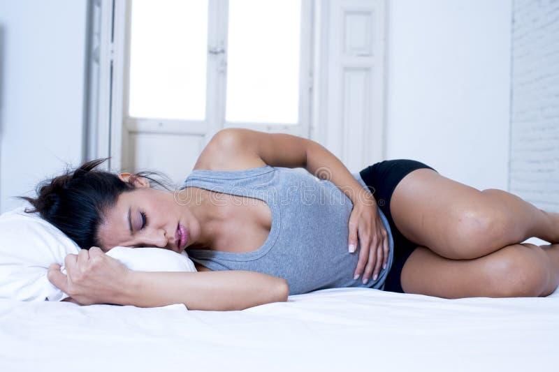 Den härliga latinamerikanska kvinnan i smärtsam uttrycksinnehavbuk som lider menstruations- period, smärtar arkivfoto