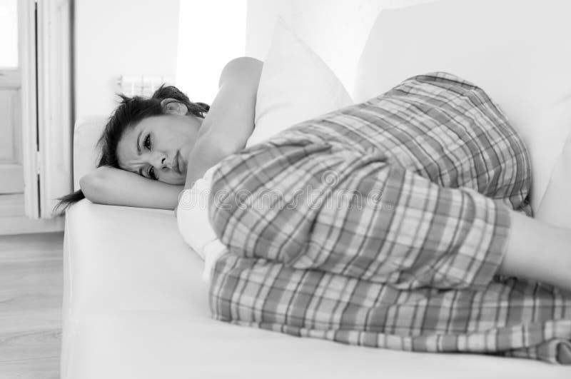 Den härliga latinamerikanska kvinnan i smärtsam uttrycksinnehavbuk som lider menstruations- period, smärtar royaltyfria foton