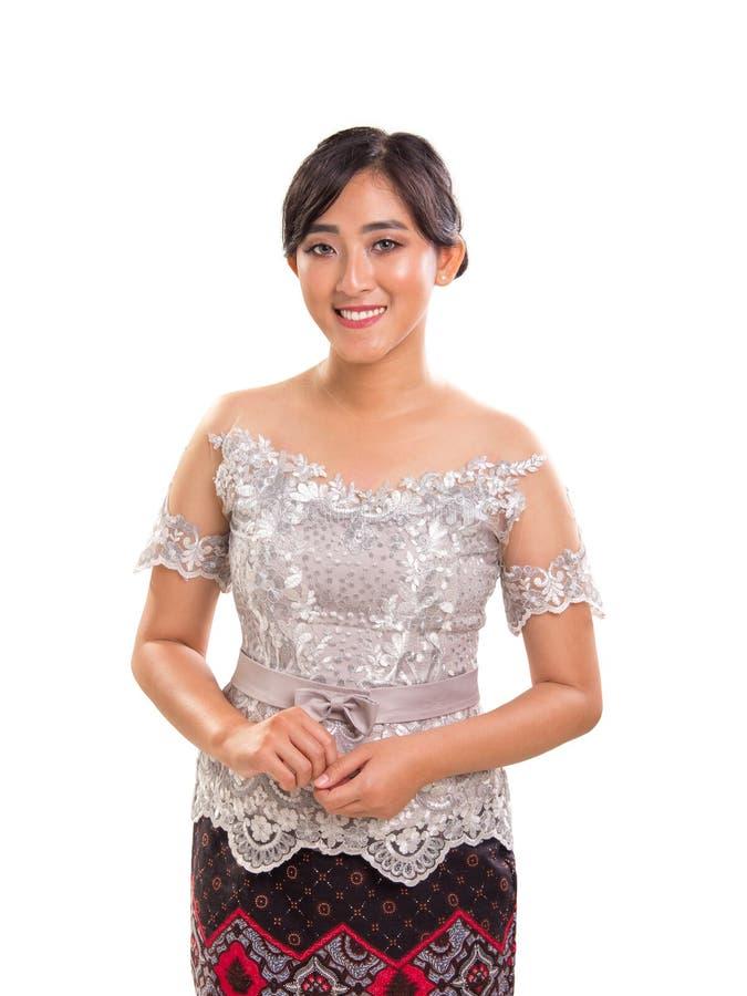 Den härliga le asiatiska damen bär moderna Kebaya dräkter, den vita bakgrundsståenden royaltyfri bild