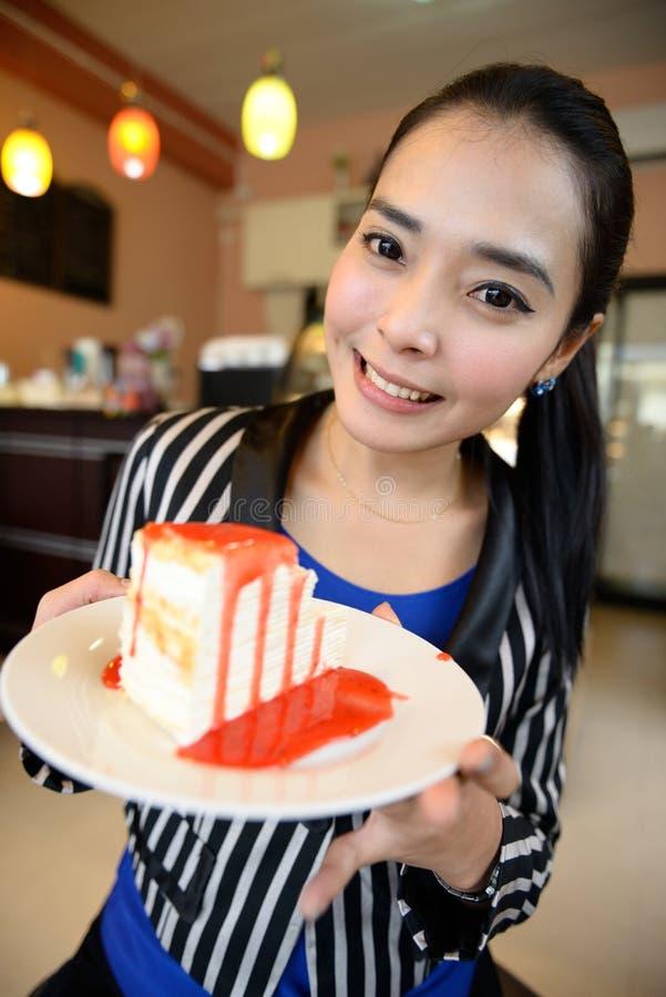 Den härliga le asiatiska kvinnan med en kaka royaltyfria foton