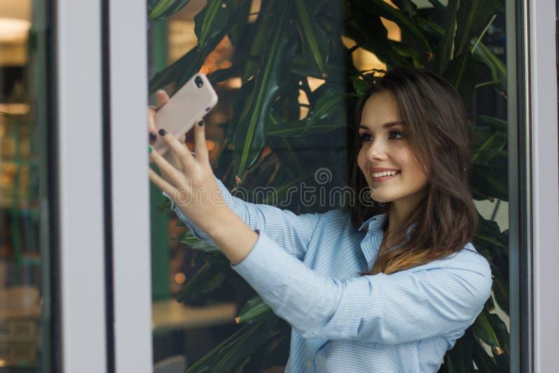 Den härliga le caucasian unga kvinnan står nära fönstret och tar ett selfiefoto arkivbilder