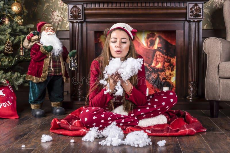 Den härliga le flickan i hem- kläderpyjamas för röd jul sitter under ett julträd nära en spis och blåser konstgjort s royaltyfria bilder