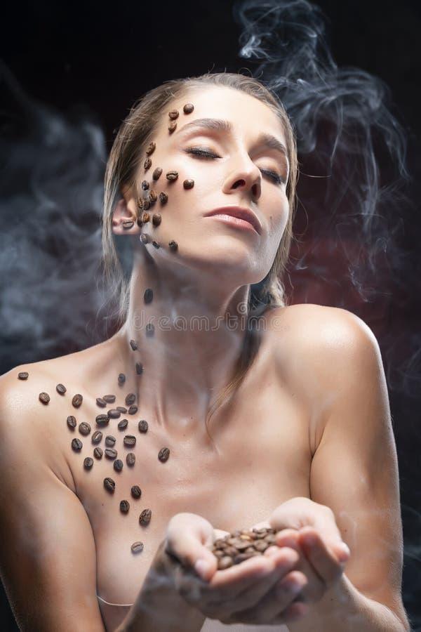 Den härliga le flickan med nakna skuldror rymmer kaffebönor i hennes händer Bönor som klibbas artistically till sund ren hud av h royaltyfri foto