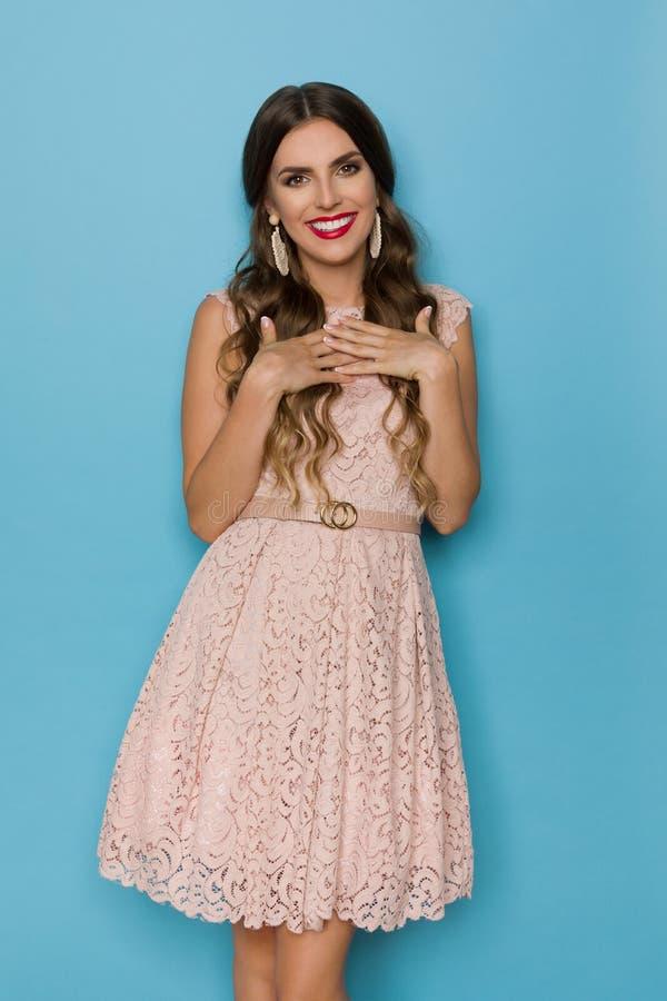 Den härliga le kvinnan i beiga snör åt Mini Dress Is Posing With händer på bröstkorg royaltyfria bilder