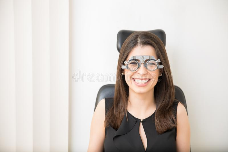 Den härliga le kvinnan som gör synförmågamätning, bär försök f royaltyfria bilder