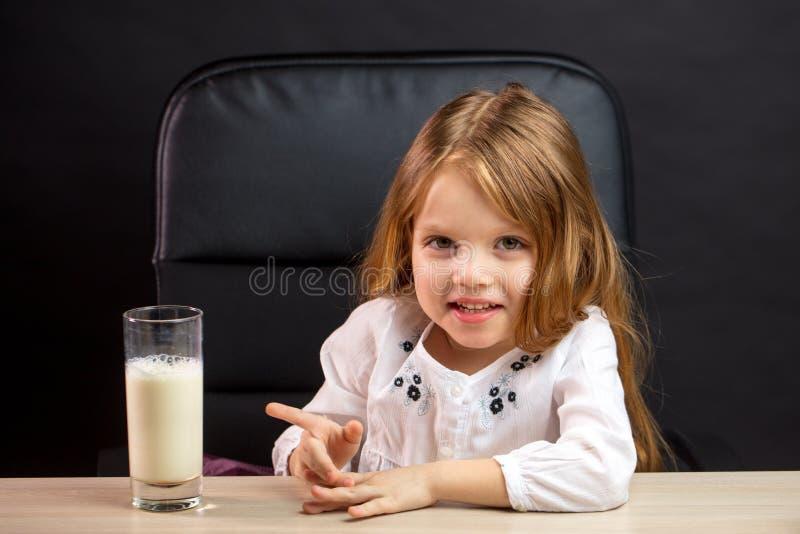 Den härliga le lilla flickan som pekar på ett exponeringsglas av, mjölkar på tabellen arkivfoton