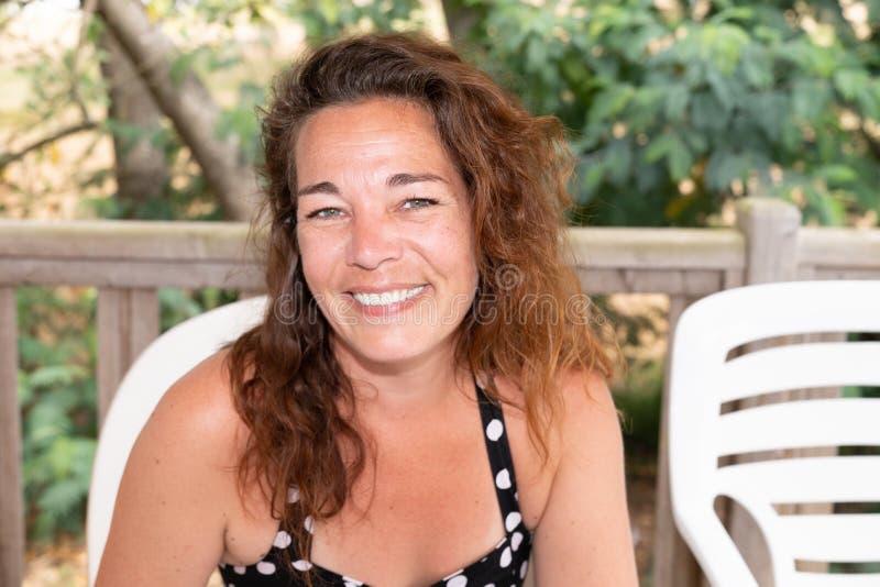 Den härliga le lyckliga kvinnamitt åldrades utomhus- grön bakgrund för ståenden arkivfoto