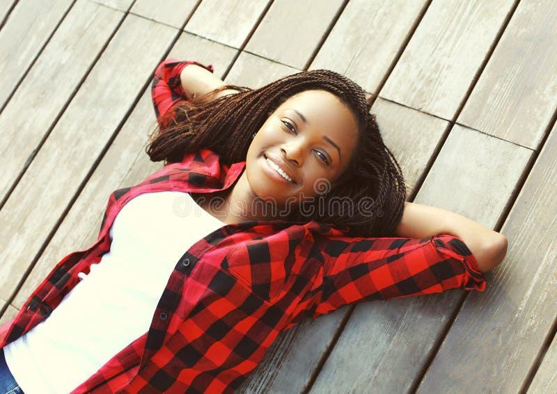 Den härliga le unga afrikanska kvinnan kopplade av på trägolv med händer bak huvudet som bär en röd rutig skjorta royaltyfria foton