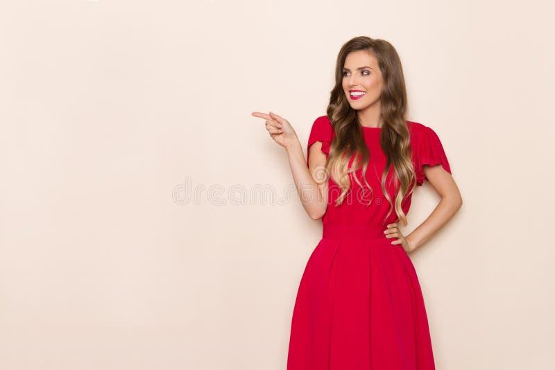Den härliga le unga kvinnan i röd klänning är peka och se bort arkivbild