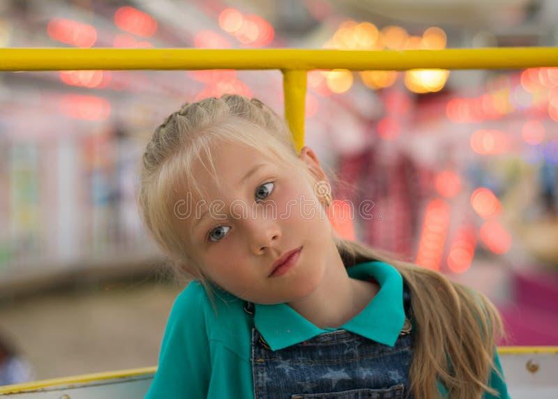 Den härliga ledsna flickan på bakgrunden av nöjesfältet tänder royaltyfri fotografi