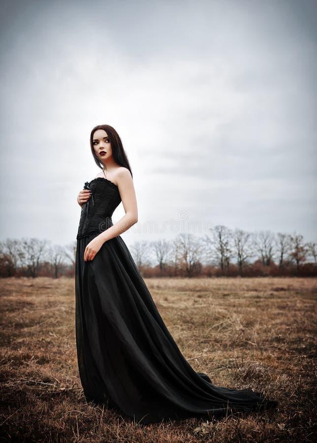 Den härliga ledsna gothflickan står i det höstliga fältet royaltyfria bilder