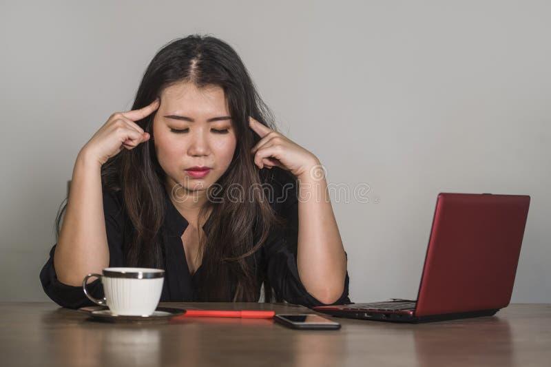 Den härliga ledsna och deprimerade asiatiska koreanska affärskvinnan som arbetar i spänning på känsla för skrivbordet för kontors royaltyfri fotografi